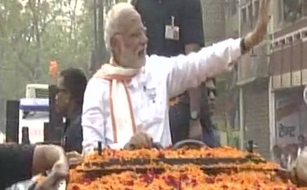 PM Modi waves towards the crowd during a road-show in Varanasi. (ANI/Twitter)