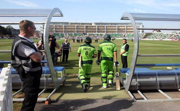 Security staff watch as Pakistani players Hafeez and Mohammad Shahzaib Hasan walk onto the pitch at Somerset County Cricket Club. (Getty Images)