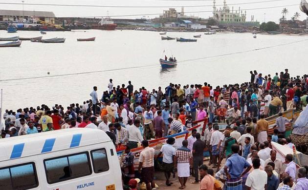 Families of fishermen wait for them to return home at Vizhinjam harbour in Thiruvananthapuram on Saturday (PTI)