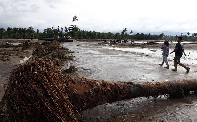 Residents walk past toppled tree after a flood by tropical storm Tembin in Lanao del Norte province, the Philippines (Source: IANS)