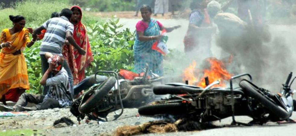 People injured in poll violence sit by the side of a road as a vehicle is set on fire by locals during panchayat polls in Nadia district of West Bengal (PTI Photo)
