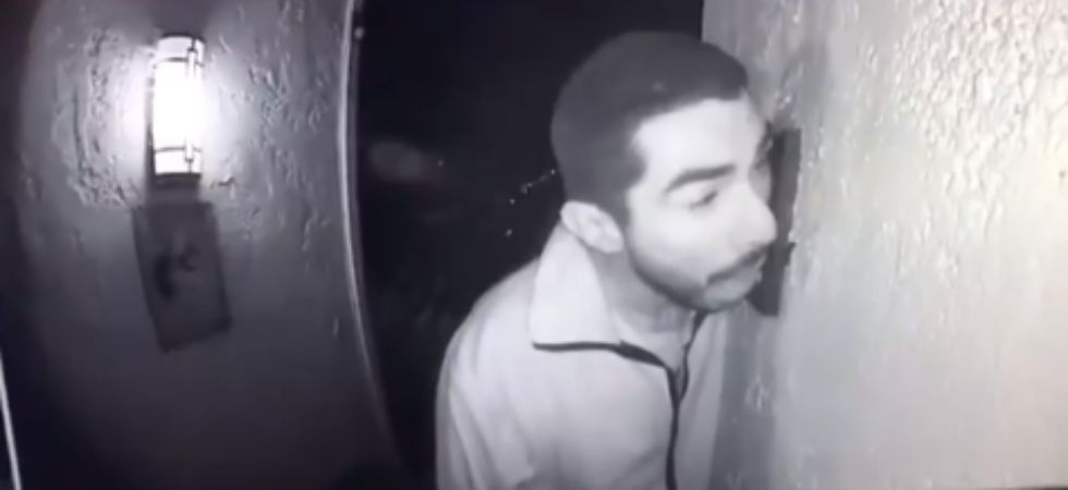 A man was caught on camera licking the doorbell./ Image: Twitter