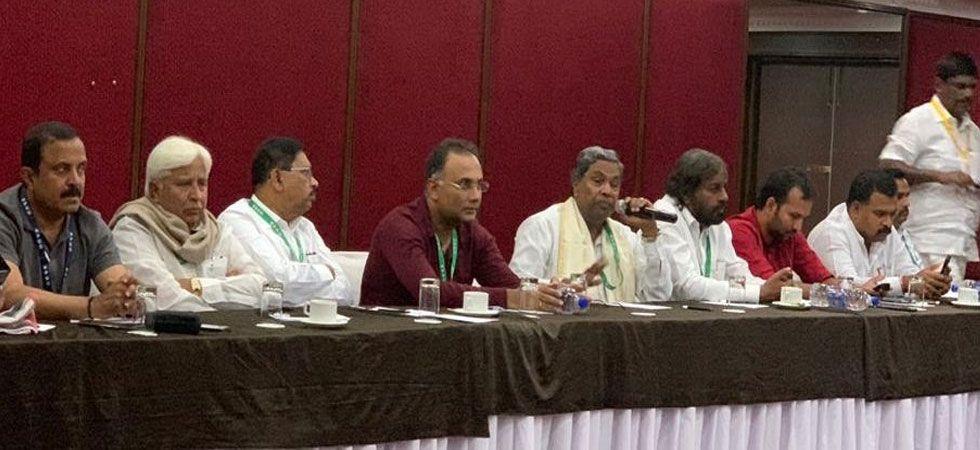 Congress Legislature Party leader Siddaramaiah (holding mike) during the CLP meeting at  Eagleton resort on Saturday. (Photo: Twitter/@INCKarnataka)