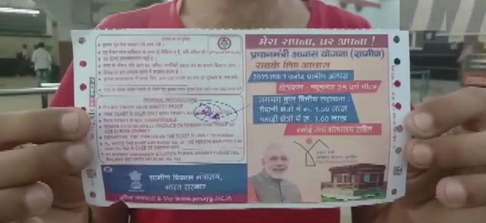 A passenger holding a train ticket with the picture of Prime Minister Narendra Modi printed on it. (ANI Photo)