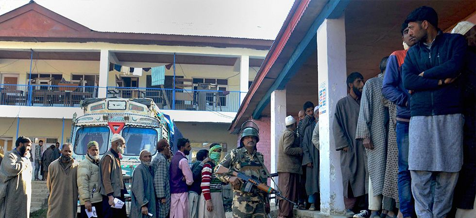 Voters queue at a polling booth in Anantnag
