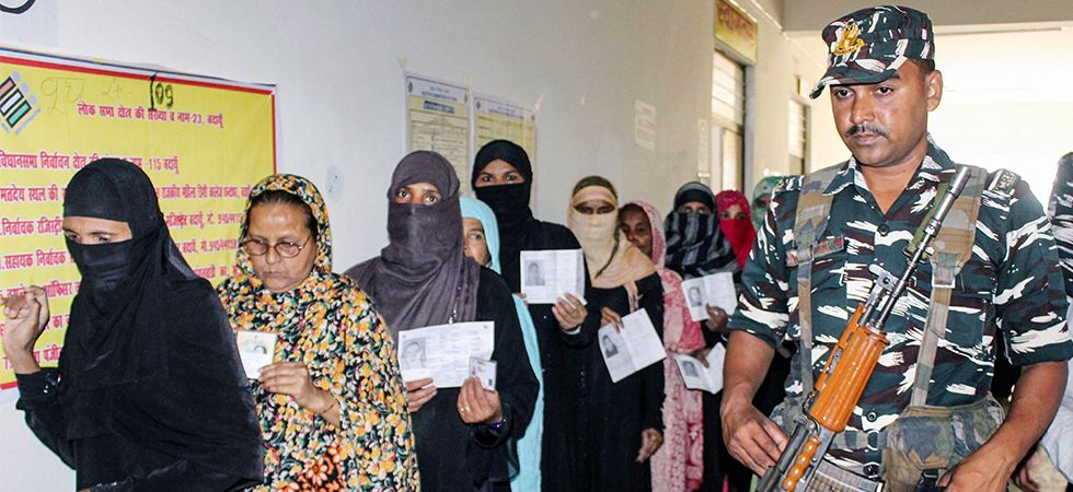 A security personnel stands guard as voters queue outside a polling station in Badaun.