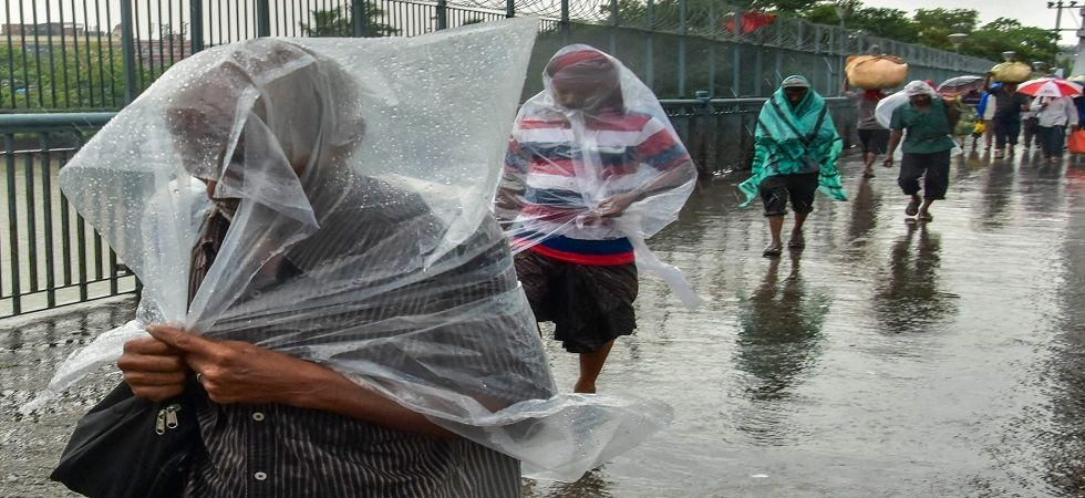 Pedestrians cover themselves with plastic sheets as they walk across the Howrah Bridge during the rain. (Photo: PTI)