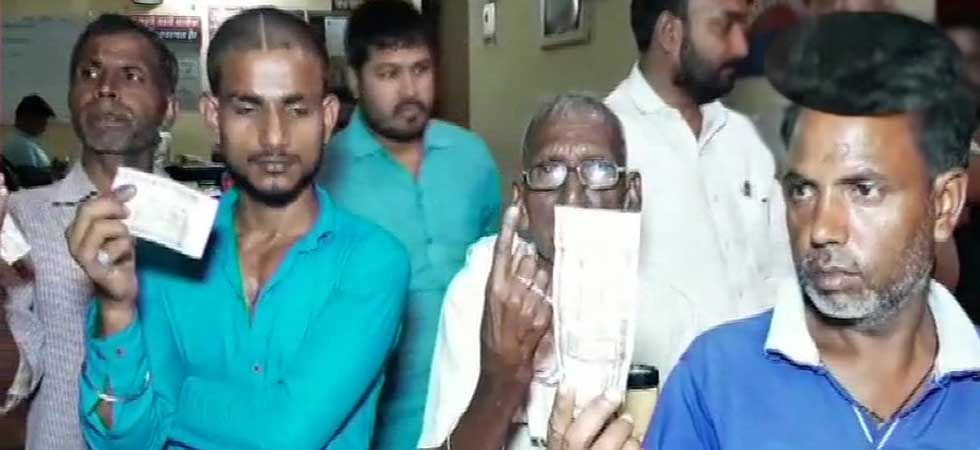 Residents of Chandauli showing Rs 500 notes they allegedly received from the BJP men. (ANI Photo)