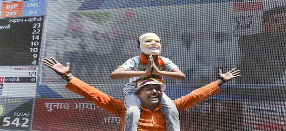 A BJP supporter celebrates at the party office in Lucknow. (Photo: PTI)
