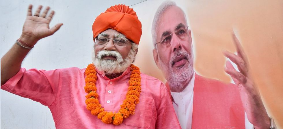 A man dressed like Prime Minister Narendra Modi poses for a photographs as BJP activists celebrate after their win (Photo Source: PTI)