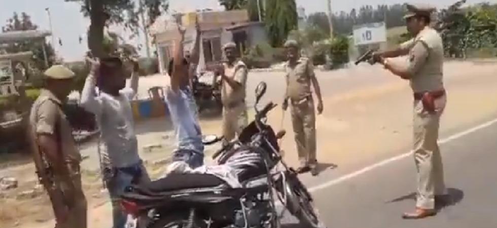 Police point gun at people during regular vehicle checking in Wazirganj, Badaun. (ANI)