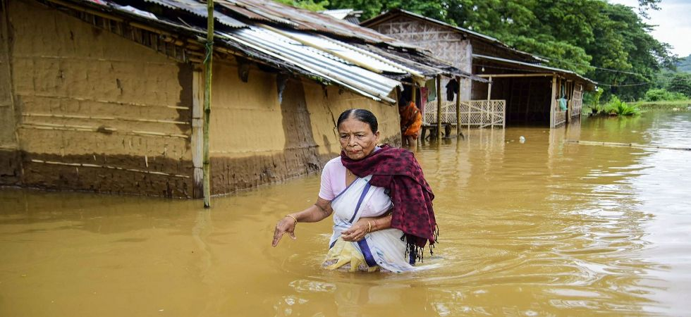 A woman wades through the water near her submerged house at a flood-affected Boithalangsu village in West Karbianglong (Photo Source: PTI)