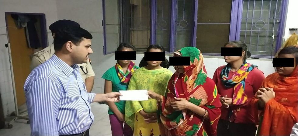 Lucknow DM paying compensation cheque to the family members of Unnao rape victim.