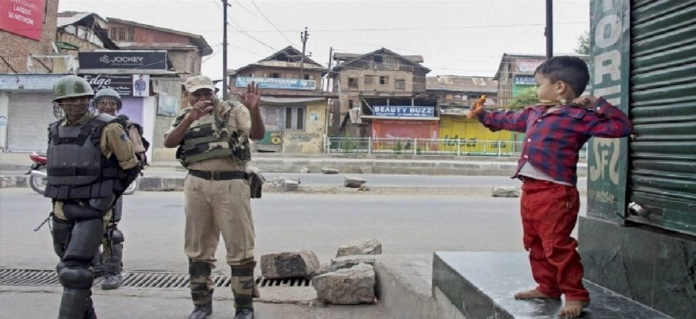 A young Kashmiri boy aiming slingshot at security personnel.
