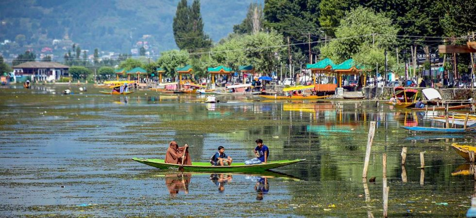 A woman rows her boat along with children across the Dal Lake, covered with weeds after being unattended for days due to restrictions (Photo Source: PTI)